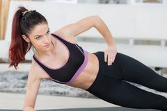 Woman while doing side plank on mat stock photo
