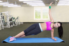 Woman doing side plank pose at gym Royalty Free Stock Images