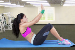 Woman doing sit up in fitness center Stock Images