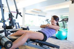 Woman doing sit up in gym. Asian young woman Stock Images