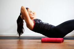 Woman doing sit up on yoga mat Royalty Free Stock Photography