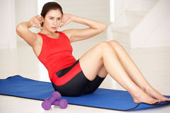 Woman doing sit-ups. In home gym on gym mat Stock Image