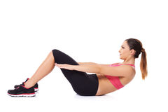 Woman doing sit ups. Fit young woman working out in a gym doing sit ups to strengthen her abdominal muscles on white Royalty Free Stock Photos