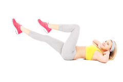 Woman doing sit-ups. A picture of a fit woman doing sit ups over white background Royalty Free Stock Photography