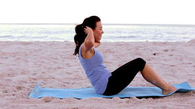 Woman doing sit ups on the beach Royalty Free Stock Images