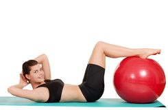 Woman doing sit ups with exercise  ball. Isolated woman doing sit ups with exercise ball on white background Royalty Free Stock Photography