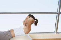 Woman Doing Sit-Ups On Exercise Ball Stock Image