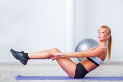 Woman doing sit-ups on the floor Stock Photography