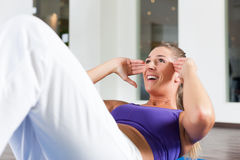 Woman doing sit ups in gym Stock Photo
