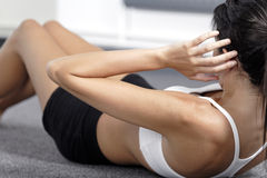 Woman doing sit ups at home. Beautiful young woman doing sit ups at home on the floor Royalty Free Stock Photo