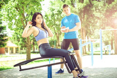 Woman doing sit ups outdoor with her trainer. Royalty Free Stock Images