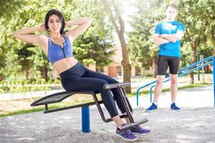 Woman doing sit ups outdoor with her trainer. Stock Photos