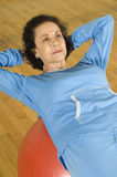 Woman Doing Sit-Ups On A Pilates Ball Royalty Free Stock Photography
