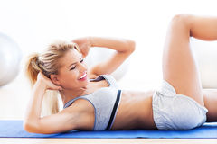 Woman doing sit-ups. Woman working out at a health club Stock Photography