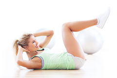 Woman doing sit-ups. Woman working out at a health club Stock Images