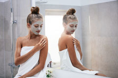 Woman doing skin treatment after bath. Beautiful young woman sitting in bathroom by the mirror with face mask. Female doing skin treatment after bath stock photos