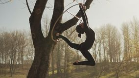Woman doing some acrobatic elements on aerial hoop outdoors stock footage