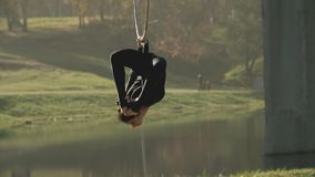 Woman doing some acrobatic elements on aerial hoop outdoors. Flexible girl stock video footage