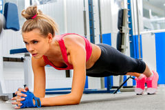 Woman doing some push ups in gym. Young woman doing some push ups in gym stock image