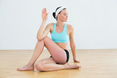 Woman doing the spine twisting pose at fitness studio Stock Photography