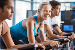 Woman doing spinning. Fitness happy women on stationary bicycle doing spinning at gym. Fit young women working out on bike. Smiling girl exercising with group of Royalty Free Stock Photo