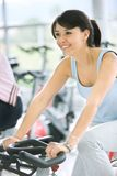 Woman doing spinning in a gym Stock Images