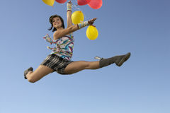 Woman Doing Splits In Air holding Balloons Stock Images