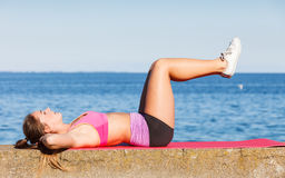 Woman doing sports exercises outdoors by seaside Stock Images