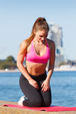 Woman doing sports exercises outdoors by seaside Stock Photos