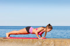 Woman doing sports exercises outdoors by seaside Royalty Free Stock Photography
