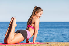Woman doing sports exercises outdoors by seaside Royalty Free Stock Image