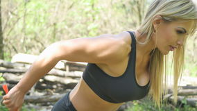 Woman doing sports in the forest. Doing triceps exercises Stock Image