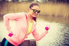 Woman exercising with dumbbells outdoor Stock Images