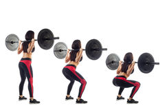 Woman doing squat  with a barbell. Young athletic brunette woman in black leggings with a red strip and black short top doing squat with a barbell, hands behind Royalty Free Stock Photo