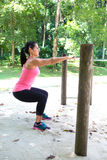 Woman doing squat exercise by the exercise bar in the park. Beautiful strong woman doing squat exercise by the exercise bar in the park royalty free stock images