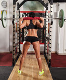 Woman doing squats with barbell on neck Royalty Free Stock Photo