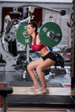 Woman doing squats with barbell on neck Stock Photos