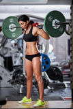 Woman doing squats with barbell on neck Stock Images