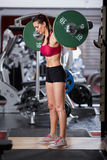 Woman doing squats with barbell on neck Royalty Free Stock Images