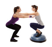 Woman doing squats on a bosu ball, helped by the peronal trainer. Studio shot of women doing squats on a bosu ball, helped by the personal trainer, isolated over Stock Images