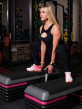 Woman doing squats with a dumbbell on a box Royalty Free Stock Images