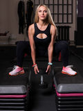 Woman doing squats with a dumbbell on a box Stock Photos
