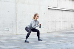 Woman doing squats and exercising outdoors Royalty Free Stock Photo