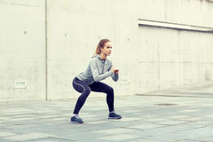 Woman doing squats and exercising outdoors Stock Images