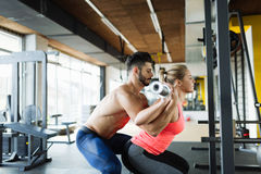 Woman doing squats with her personal trainer Royalty Free Stock Photography