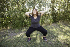 Woman doing squats Stock Images