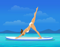 Woman doing Stand Up Paddling Yoga on Paddle Board. SUP yoga workout Stock Photo