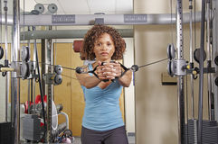 Woman doing standing rows in a gym Stock Images