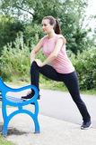 Woman Doing Stretches Using Park Bench royalty free stock photography