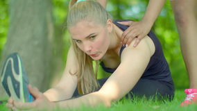 Woman doing stretching exercise on green grass at park. Fitness woman stretching outdoor. Beautiful sport woman doing fitness exercise. Outdoor workout. Two stock footage